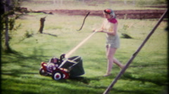 2299 - mom cuts the grass in the backyard at home - vintage film home movie Stock Footage