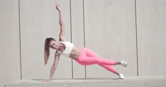 Sporty Pretty Young Woman Doing a Side Plank Exercise with One Arm Raised on a W Stock Footage