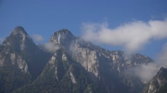 Clouds and fog covering mountains peak, blue sky Stock Footage