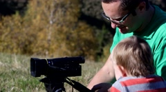 Father learning his son to use photo camera outdoor Stock Footage