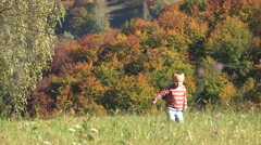 Cute little child walking in autumn forest, wondering in nature - stock footage