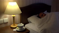 Sick man resting on bed, restless, nigfhtmare, pills and tea, nightlight Stock Footage