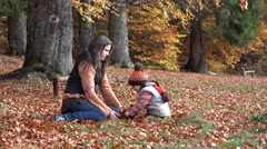 Stock Video Footage of Mother and child playing with autumn leaves, together in nature