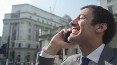 4k, happy businessman on mobile phone in london city street Stock Footage