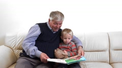 Grandparents reading a book for grandchild, happy senior, enjoy a life story Stock Footage