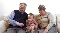 Different generations, grandparents and grandson playing with tablet computer Stock Footage