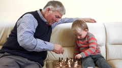 Stock Video Footage of Grandparent lesson, grandfather explain to grandson intelligent game, chess