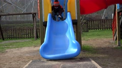 Kid with little toy car on playground slide in the park Stock Footage