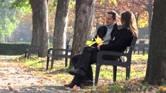 Stock Video Footage of Beautiful mother and father sitting on bench in park, son playing in nature