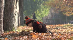 Lovely child playing with autumn leaves in park, beautiful nature - stock footage