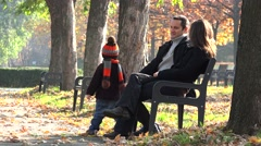 Child playing with a stick, parent resting on a bench in the park, autumn nature Stock Footage