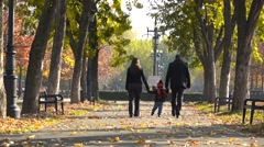 Young parent and child holding hands walking on autumn alley in park, gorgeous  Stock Footage