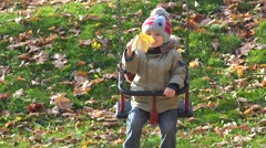 Adorable child with a yellow leaf smiling on swing, beutiful autumn - stock footage