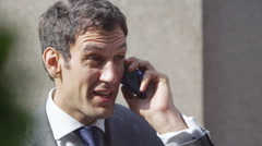 4k, confident businessman closes deal on smart phone outside office building Stock Footage