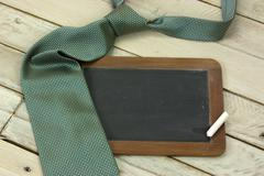 Tie and blackboard on wooden background - stock photo