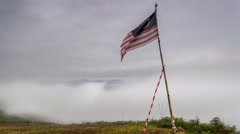 Ageing Malaysian Flag On A Foggy Hill With Sea of Clouds Stock Footage