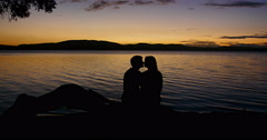 A romantic young couple sit together and share a kiss by a lake at sunset - stock footage