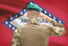 Soldier saluting to US state flag series - Arkansas Stock Photos