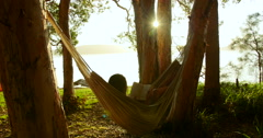 Woman relaxes reading book in hammock swaying gently, in wood on beach at sunset Stock Footage
