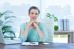 Attentive businesswoman looking at the camera - stock photo