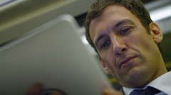 4k, close-up of handsome businessman using digital tablet underground train - stock footage
