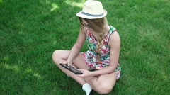 Happy young Caucasian brunette woman with tablet in park on sunny summer day sit - stock footage