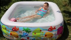 Girl swiming in inflatable pool on the garden Stock Footage