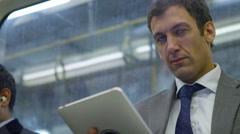 4k, Attractive businessman working on digital tablet on city underground train Stock Footage