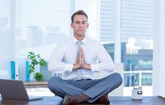 Zen businessman doing yoga meditation - stock photo