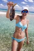 Girl in bikini holding a fish on a beach in the Cook Islands Stock Photos