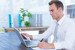 Attentive businessman writing on notebook Stock Photos