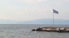 Greek flag in the wind, rocky shore and mainland in far distance Stock Footage