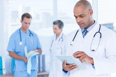 Attentive doctor using his tablet Stock Photos