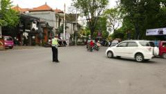 Active police officer regulate traffic on busy balinese junction, loud whistling Stock Footage