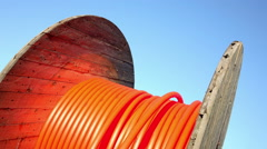 Zoom-in and rotation of wooden cable drum with orange cable Stock Footage