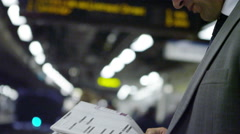 4k Businessman drinking coffee & reading newspaper on train platform Stock Footage