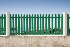 Green fence in front of the sea Stock Photos