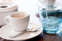 Hot aromatic espresso cup and cold water in glass Stock Photos