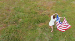 Girl waving american flag while walking on grass Stock Footage
