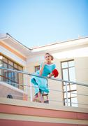 Stock Photo of Enjoyment. Fashion model woman with blowing dress over blue sky, outdoors. young