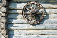 Wooden wheel on the log wall. Stock Photos