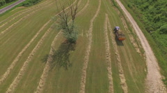 AERIAL: Farmer picking up sun dried grass with tractor trailer Stock Footage