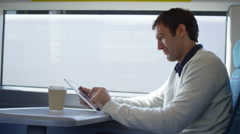 4k Smiling casual man using computer tablet on train journey.  Stock Footage
