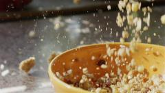 SLOW MOTION CLOSE UP: Whole grain cereal falling into bowl - stock footage