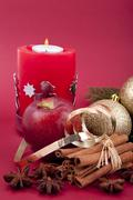 christmas decoration red apple, cinnamon, anise and tree on red background - stock photo