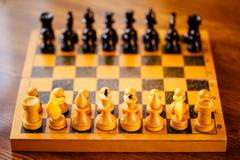 Ancient wooden chess standing on chessboard - stock photo