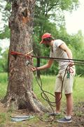 Man prepares the equipment fixes secures the rope to the tree for slacklining Stock Photos