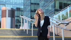 Young woman standing on the stairs and talking on a cellular phone - stock footage