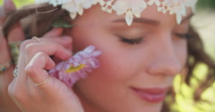 Boho teenager iputting pink daisy flower behind her ear - stock footage