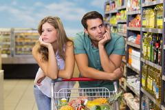 Serious brght couple buying food products - stock photo